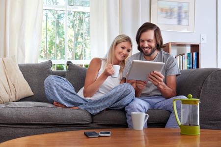 Pares de sorriso com caneca de caf� computador tablet no sof� sof� em casa
