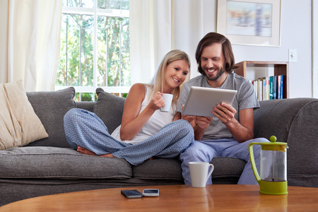 smiling couple with tablet computer coffee mug on sofa couch at home Foto de archivo