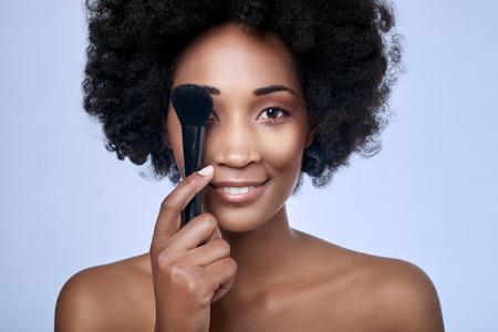 完璧な肌、メイクアップ ブラシ 1 つ目は、明るい青の背景に分離をカバーを保持している滑らかな肌と美しい黒アフリカ モデル