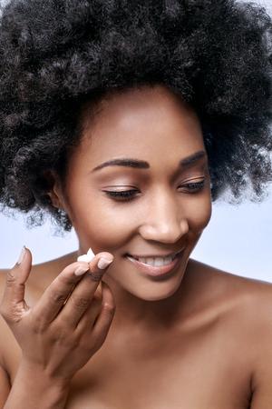 dedo: modelo africano negro hermosa con crema facial hidratante en sus dedos