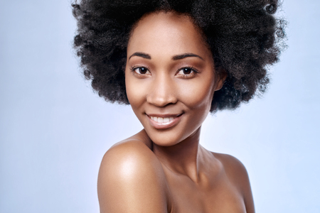 Portrait of beautiful black african model smiling in studio with smooth complexion flawless skin 스톡 콘텐츠