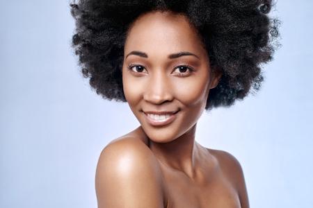 부드러운 안색의 피부가있는 스튜디오에서 웃는 아름다운 검은 아프리카 모델의 초상화 스톡 콘텐츠