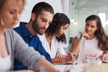 productividad: compa�eros de trabajo reunidos en la sala de juntas para discutir ideas para productividad de la empresa en el trabajo Foto de archivo