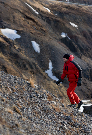 rugged man: Man in wilderness rugged mountain landcape determined to climb to the summit in red snow gear Stock Photo