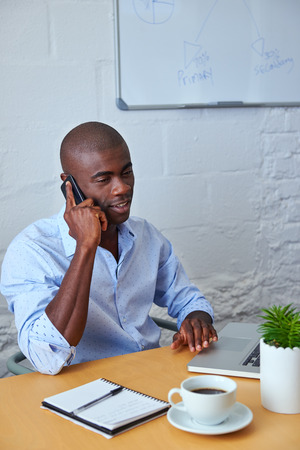 man at work: professional african black man talking on mobile cell phone to clients in office
