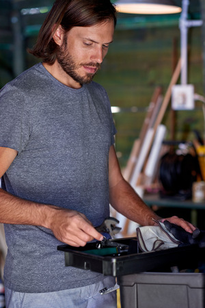 sorting out: handy man sorting out his tools in his home workshop
