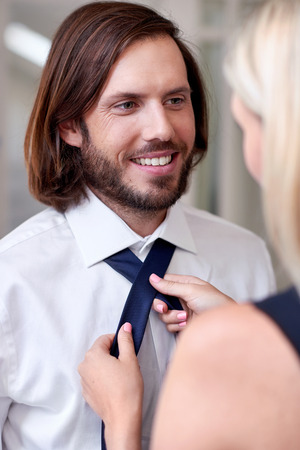 formal dressing: woman helping man with tie early morning for work formal event Stock Photo