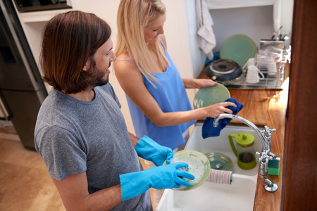 doing: Happy caucasian couple doing household chores in the kitchen Stock Photo
