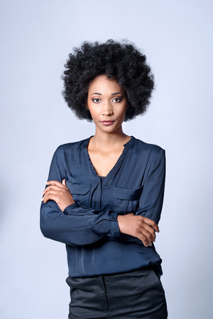isolated woman: Confident self assured black african business woman with afro in studio, isolated on grey background