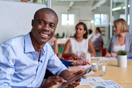 Retrato do homem de neg�cio preto profissional africano durante colegas de trabalho sala de reuni�es com o computador tablet que tomam notas