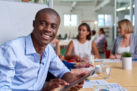 persone nere: Ritratto di professionista africano uomo d'affari nero durante i colleghi sala del consiglio l'incontro con computer tablet prendere appunti
