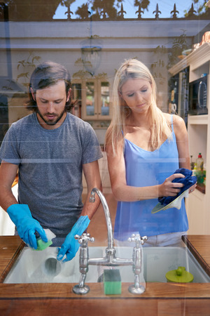 lavar trastes: Caucásica par hacer las tareas del hogar joven en la imagen de la cocina a través de la ventana Foto de archivo