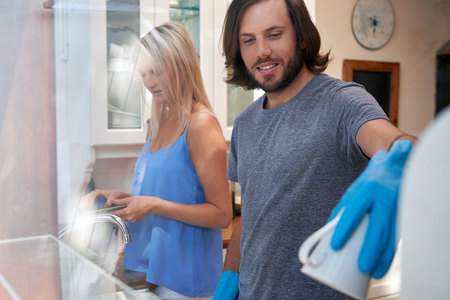 apartment cleaning: Happy caucasian couple doing household chores in the kitchen Stock Photo