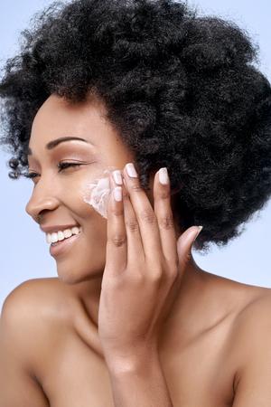 masaje facial: Bella modelo africano negro con piel impecable cutis suave aplica la crema hidratante crema de cara a la mejilla