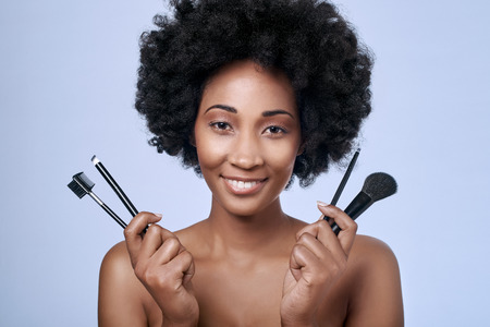 complexion: Beautiful black african afro model with flawless complexion and smooth skin holding up different make-up brushes for different applications