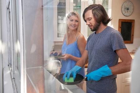 lavar trastes: Caucásica par hacer las tareas domésticas felices en la cocina