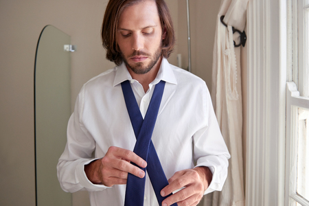 morning routine: young professional man doing morning routine shirt and tie in bathroom Stock Photo