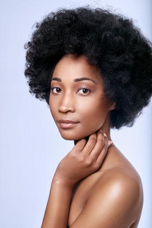 Headshot van mooie jonge zwarte Afrikaanse model in de studio met een egale teint vlekkeloze huid