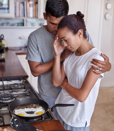 Man comforting supporting hugging his partner wife who is feeling emotional sad depressed over kitchen stove at home Stok Fotoğraf