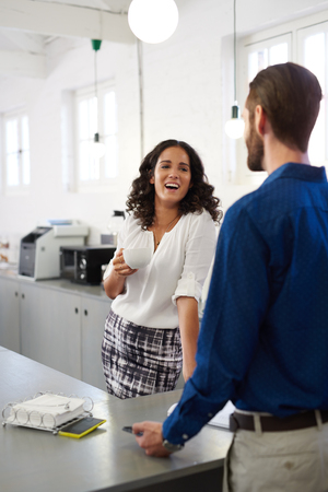 flirt: young business woman and man taking coffee break chatting in office