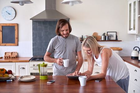kitchen device: couple bonding and enjoying morning coffee with tablet computer in kitchen at home