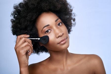 mujer maquillandose: Bella modelo africano negro con cutis perfecto y la piel lisa sosteniendo un pincel de maquillaje en su mejilla aislado en fondo azul claro