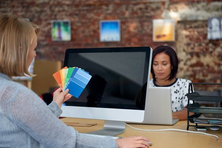 open plan: creative graphic designer woman comparing colour swatches in open plan agency