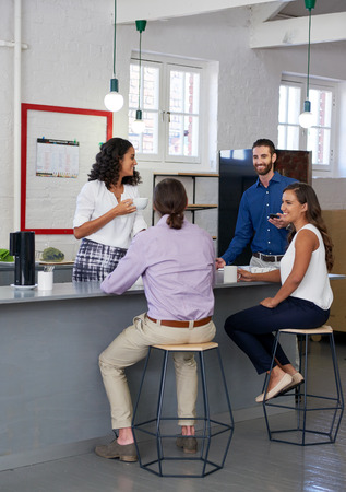 Business colleagues having coffee tea break in trendy modern open plan startup office kitchen