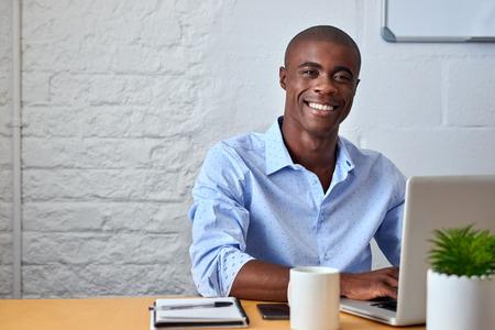 trabajando: retrato de joven apuesto hombre de negocios negro africano que trabaja en la computadora port�til en el escritorio de oficina Foto de archivo