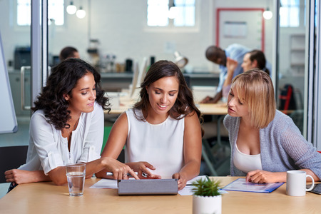 office meeting: diverse multiracial colleagues discussing tech startup business ideas on tablet computer device Stock Photo