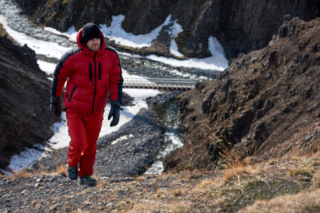 rugged: Man in wilderness rugged mountain landcape determined to climb to the summit in red snow gear Stock Photo