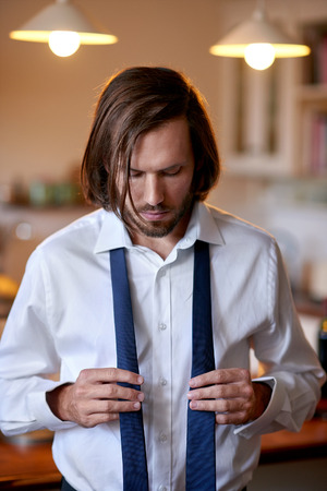 morning routine: young professional man doing morning routine shirt and tie at home