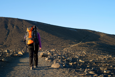 travel gear: Young asian woman hiking in Iceland with backpack and outdoor gear on vacation holiday travel adventure