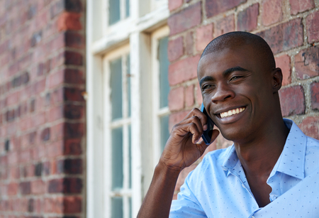 야외의 모바일 휴대 전화에 말하는 젊은 아프리카 계 미국인 흑인 사업가