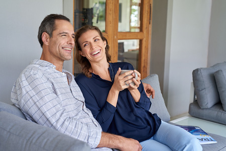 couple relaxing: Happy Caucasian couple laughing and smiling enjoying coffee together outside sitting on terrace couch