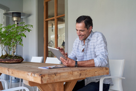 patio: Handsome mature man sitting on his home patio looking up things on his tablet device