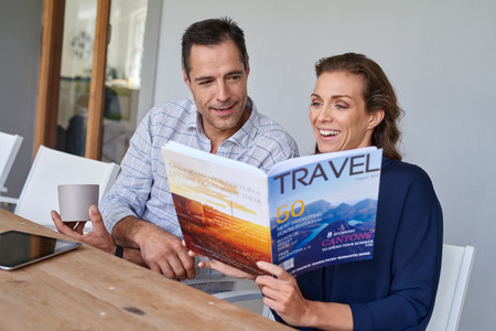 happy wedding: smiling Caucasian couple sitting at outdoor terrace patio having coffee and reading travel magazine Stock Photo
