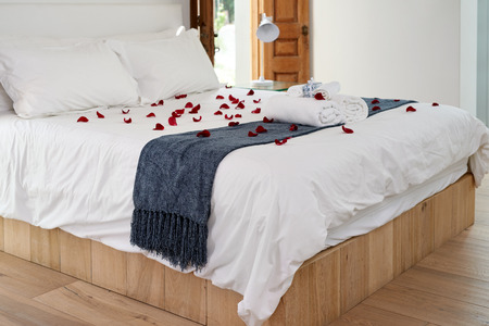 Decorated romantic hotel honeymoon bed with red rose petals and towels. Stock Photo