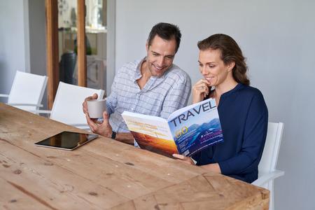 glimlachende Kaukasische paar zitten op een terras patio met koffie en het lezen van reismagazine Stockfoto