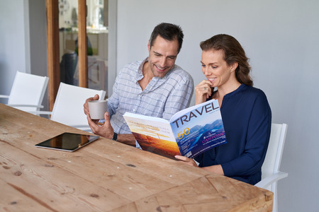 smiling Caucasian couple sitting at outdoor terrace patio having coffee and reading travel magazine Stock Photo
