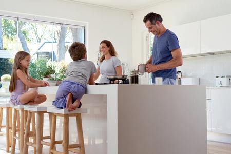 család: boldog, mosolygós, kaukázusi család a konyhában készül reggeli Stock fotó