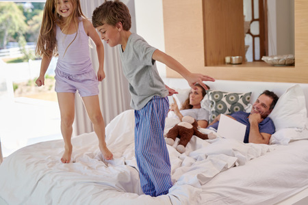 Happy children boy and girl siblings jumping on parents bed in morning