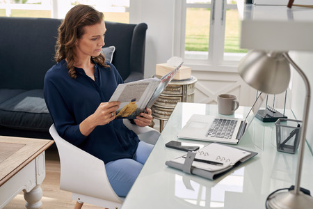 Casual businesswoman seated at home office space looking at business magazine