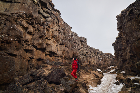 scenary: Man exploring lava rock formations in tectonic plate crack crevice in thingvellir national park iceland