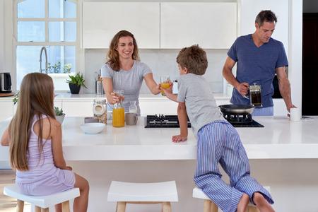 Gelukkige lachende Kaukasische familie in de keuken met ontbijt Stockfoto
