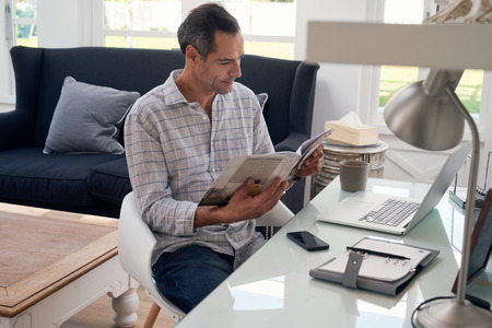 Casual mature man seated at home office space looking at business magazine with a happy expression on his face. Foto de archivo