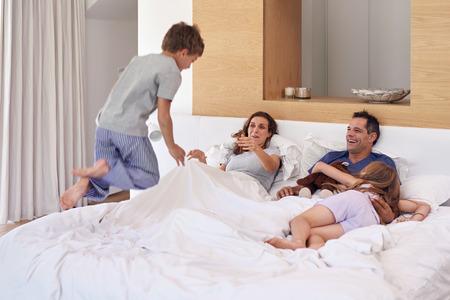 Gelukkige kinderen jongen en meisje broers en zussen springen op bed van de ouders in de ochtend