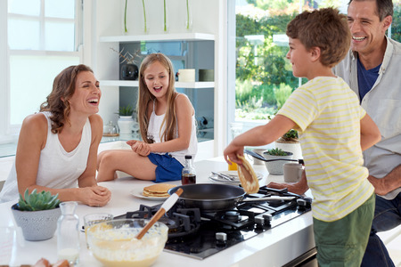 Happy caucasian family standing around stove, son making pancakes on stove Standard-Bild