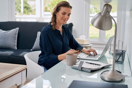 trabajando en casa: exitosa mujer de negocios maduros que mira el teléfono celular móvil mientras está en casa en el espacio de trabajo de oficina Foto de archivo