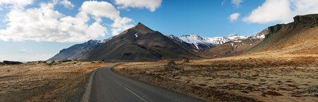 scenary: Empty deserted iceland ring road leading into beautiful mountain landscape Stock Photo